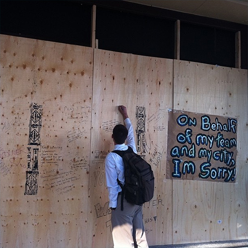 People posting messages on The Bay's boarded up windows. Photo: Zerlene