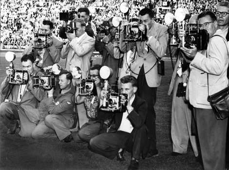 Photographers take pictures of a ceremony at the British Empire Games. At the right front is the Province's Bob Olsen, shooting photos of Earl Alexander. Photo filed August 1954. Eric W. Cable/Province