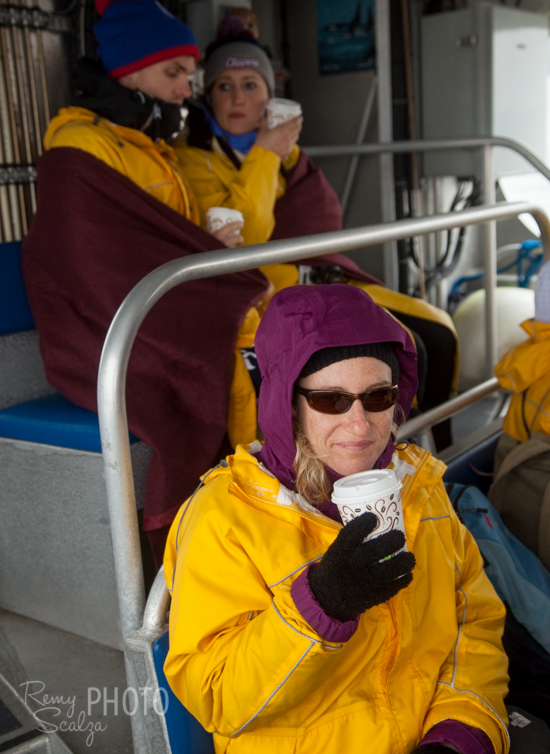 Facing uncommonly cold June conditions, passengers retreat to the covered deck to warm up.