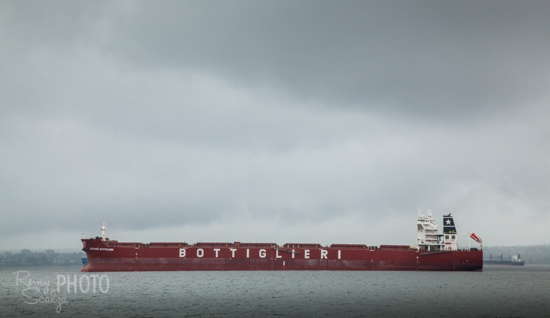 The boat speeds past massive container ships as it exits English Bay.