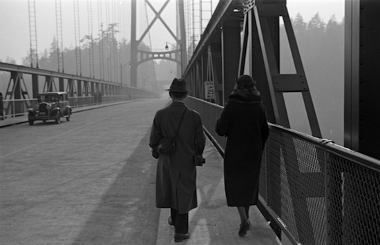 A man and woman walk across the still-relatively-new Lions Gate Bridge, 1939. City of Vancouver Archives. CVA 260-995. Photograph by James Crookall.