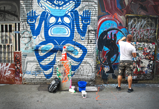 Steen installing the new wheat paste Giger piece. Photo by Ehren Seeland