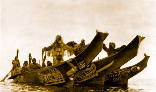 Wasp, Thunderbird and Grizzly Bear dancers perform in the bows of the three canoes as the groom's party approaches the village of the bride's father. Photograph by Edward Schwinke.  IN THE LAND OF THE HEAD HUNTERS (1914). The film has been restored by UCLA Film & Television Archives in association with the Field Museum of Natural History and Milestone Film and VIdeo.