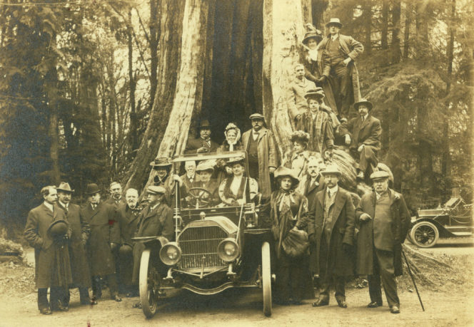 A large group of people pose with car in front of the Hollow Tree in Stanley Park. Photo taken in 1909.