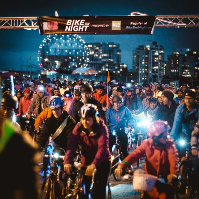 A group of cyclists rides in front of Science World at the Bike the Night Event in Vancouver, BC