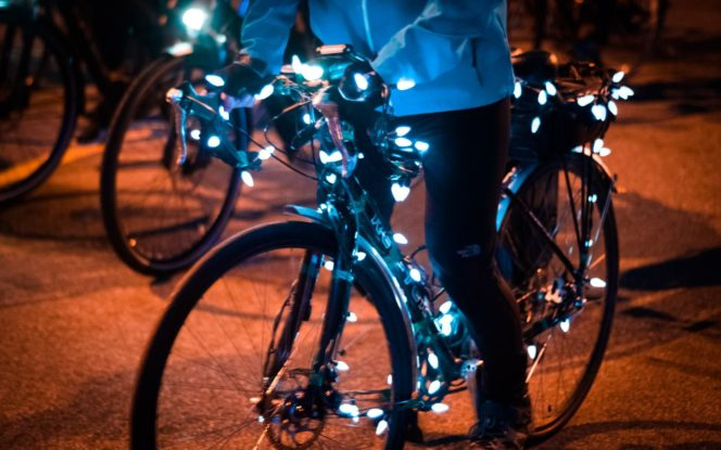 A cyclist rides a bike covered in twinkle lights at the Bike the Night event in Vancouver, BC