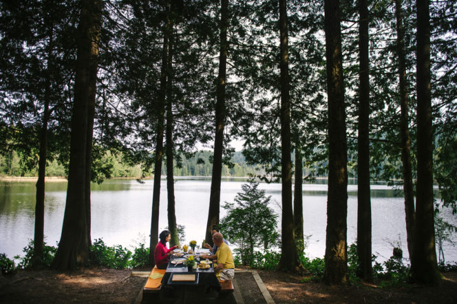 People eating at a picnic table besides Killarney Lake on Bowen Island near Vancouver, BC