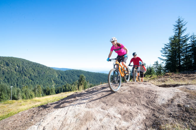 Mountain bikers on a rock slab at Grouse Mountain in North Vancouver, BC
