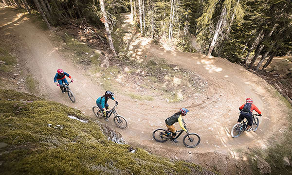 Mountain bikers descend a curve in the mountain bike park in Whistler, BC