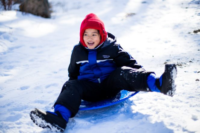 A boy riding a sled in the snow