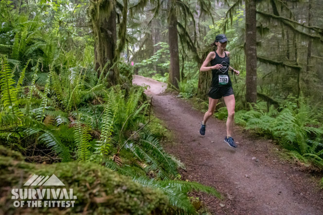 A female runner on a forested trail during the Survival of the Fittest trail running race in Squamish