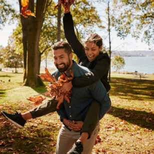 A couple enjoys fallen leaves at a Vancouver Park