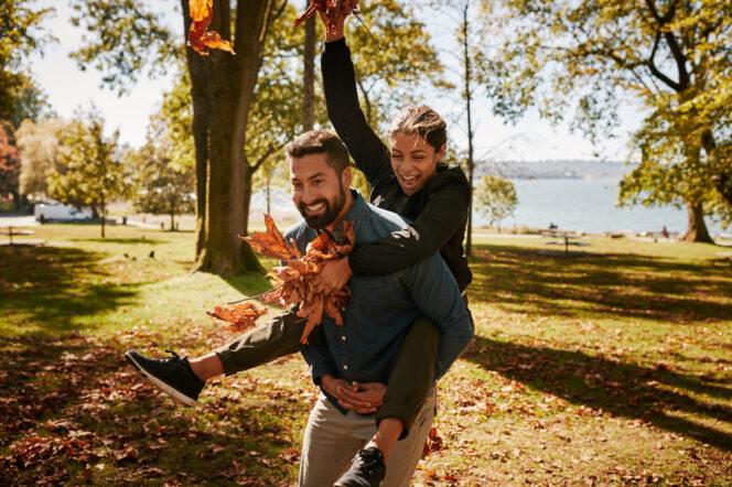 A couple enjoys fallen leaves at a Vancouver Park