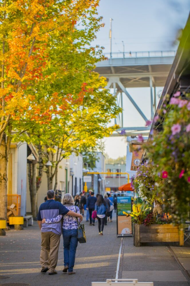 People walk past trees with fall colours on Granville Island in Vancouver