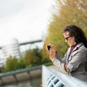 Woman taking photo on iPhone autumn in Vancouver