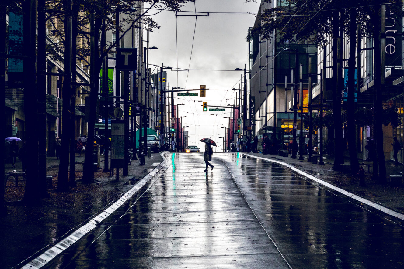 Person walking in the rain on Dowtown Vancouver street
