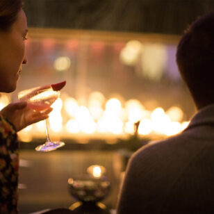 Couple drinking cocktails by the cozy fireplace at the Fairmont Pacific Rim.