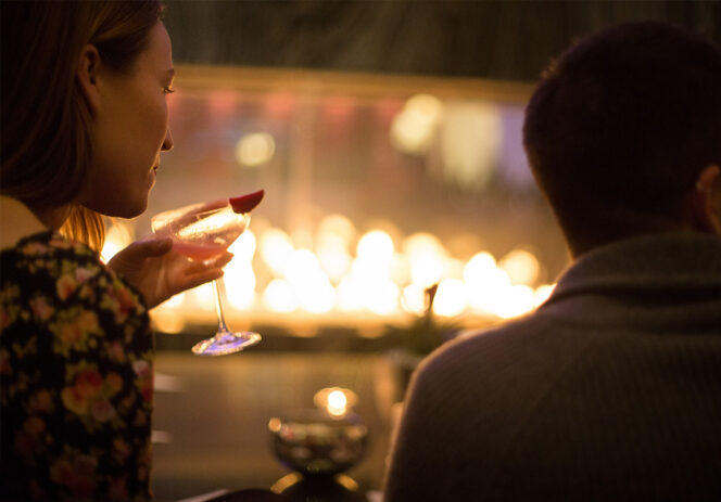 Couple having a cocktail in front of a fireplace at the Vancouver Fairmont Pacific Rim Hotel
