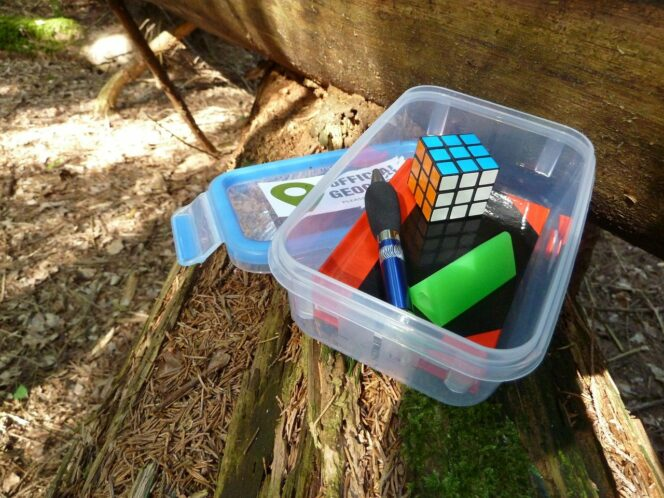 Open geocache with treasure inside.