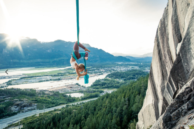 A woman suspended from aerial silks on the Stawamus Chief