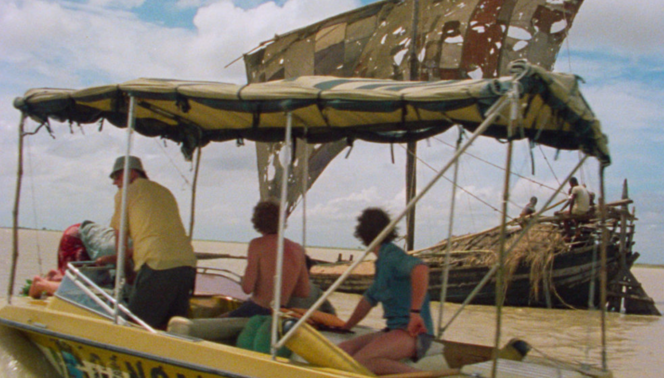 Men sit on a boat with a tattered canopy - still from the film Ocean to Sky