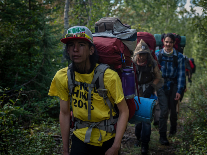 Indigenous youth hike through the forest in a still from the film In the Footsteps of Our Ancestors