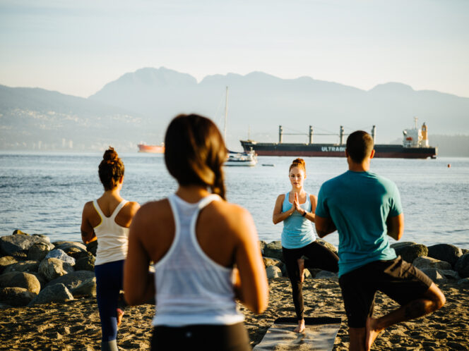 People doing yoga on a beach in Vancouver