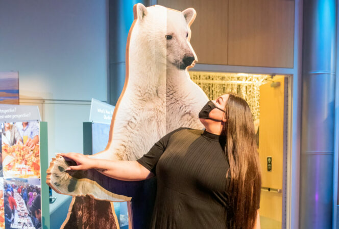 Woman standing in front of a polar bear cut out at Science World in Vancouver