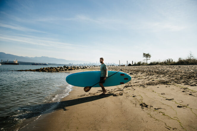 A man carries a paddleboard to the beach in Vancouver