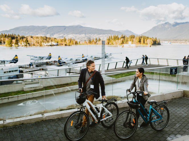 Two people e-biking on the Coal Harbour Seawall in Vancouver