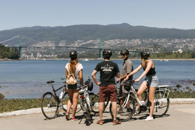 A group of cyclists with e-bikes on the Stanley Park seawall on a Cycle City Tour