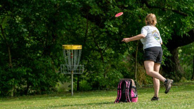 A woman throwing a disc at a disc golf basket